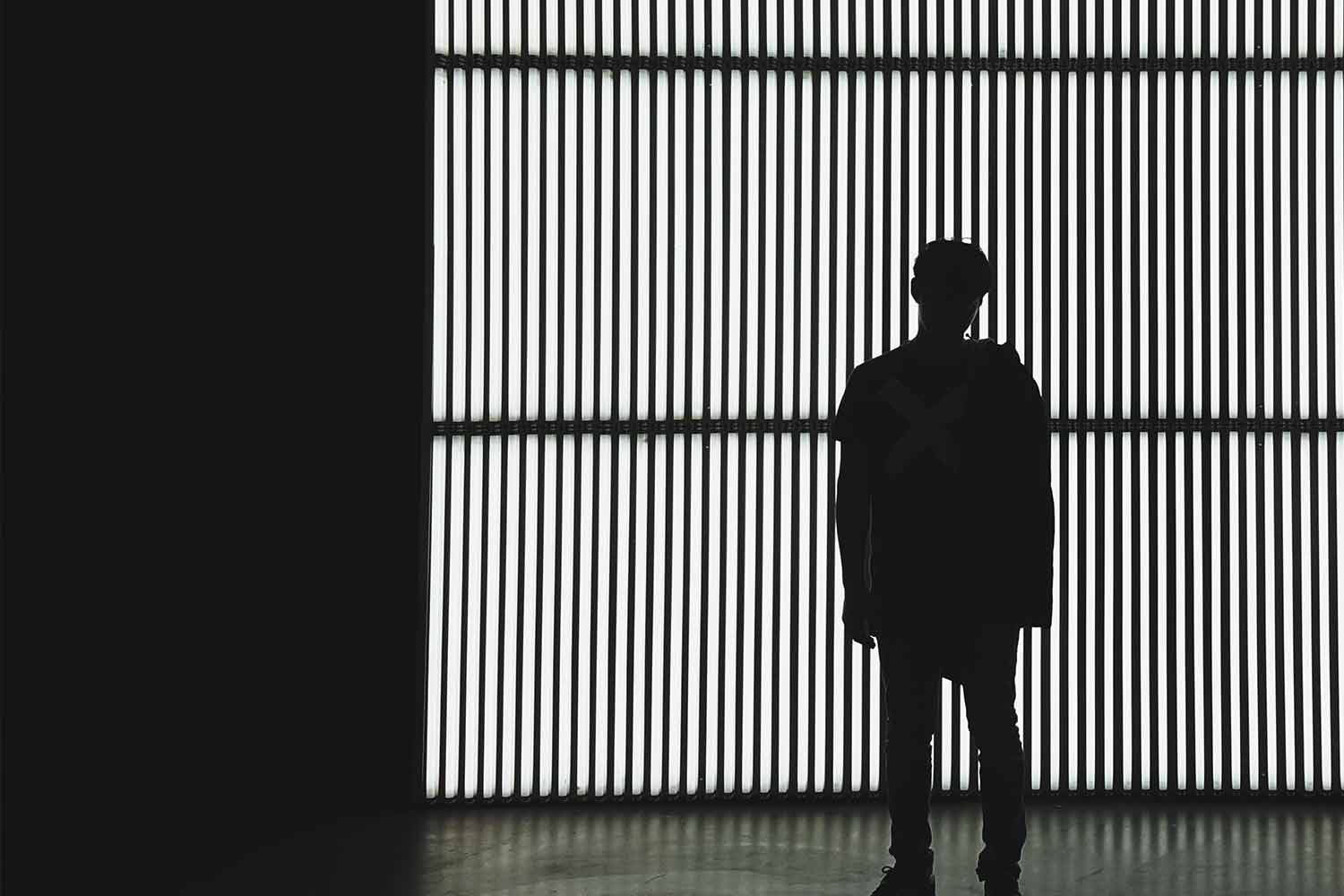 silhouette of a man against striped background