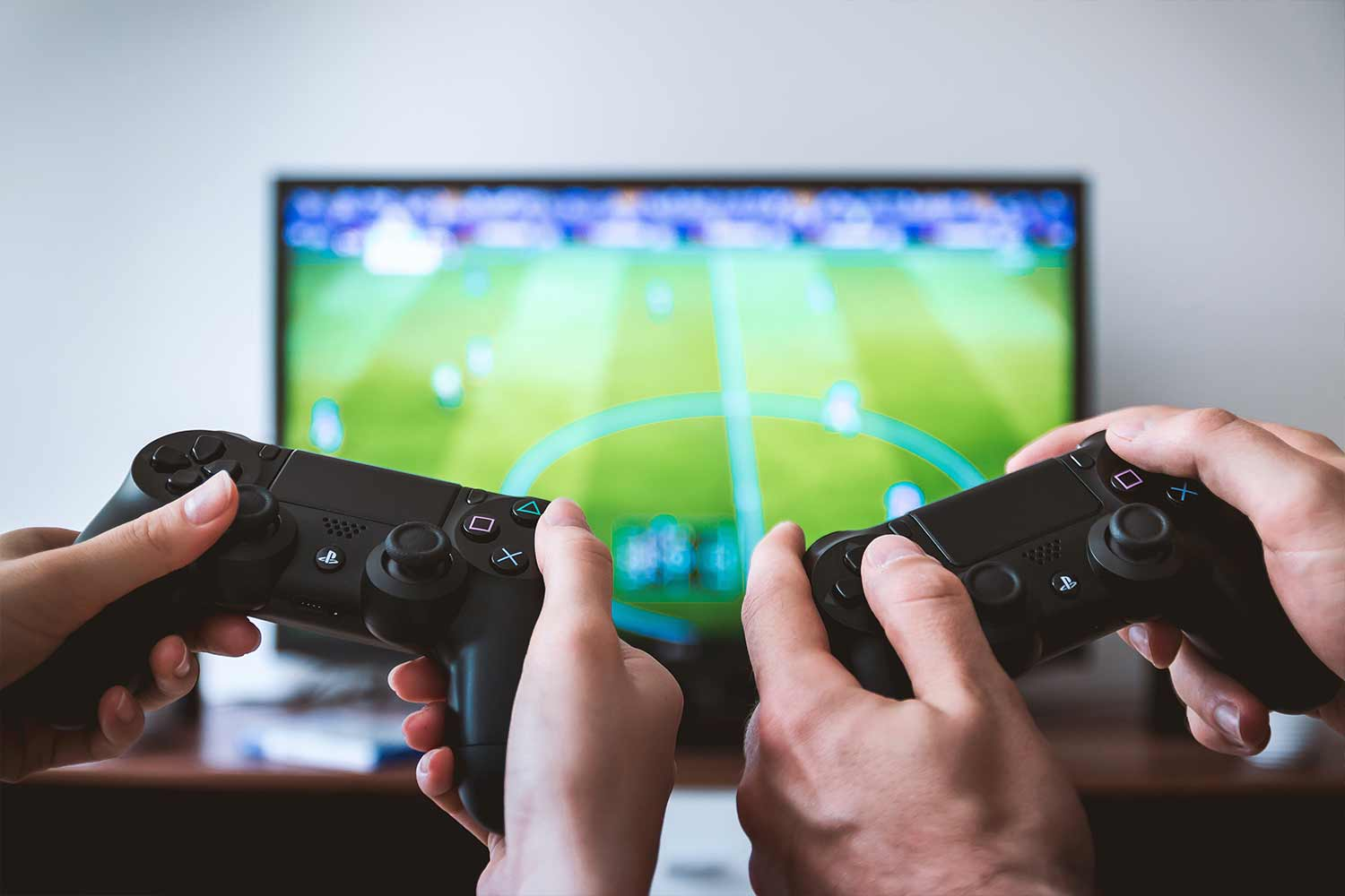 video-game-controllers-with-tv-in-background.jpg