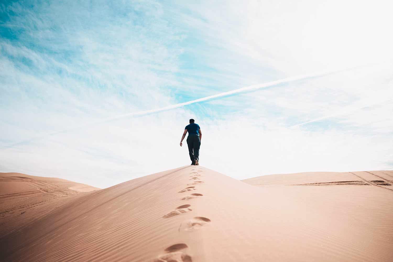 Man-walking-into-desert