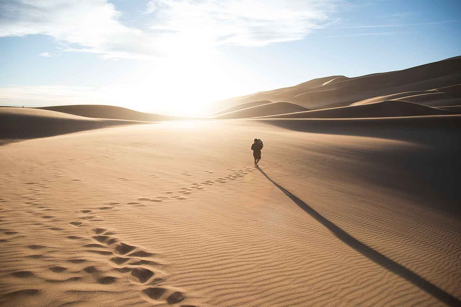 man-walking-through-sand-dunes